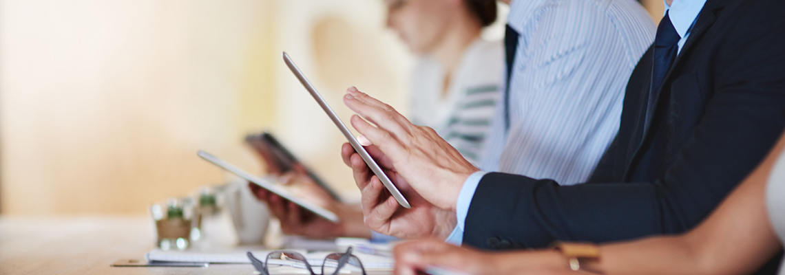 Image of a row of people at a table, with focus on hands using a tablet