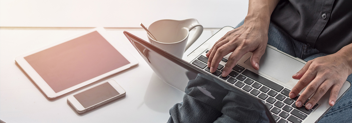 Image of hands on a laptop next to a tablet and mobile phone and coffee mug