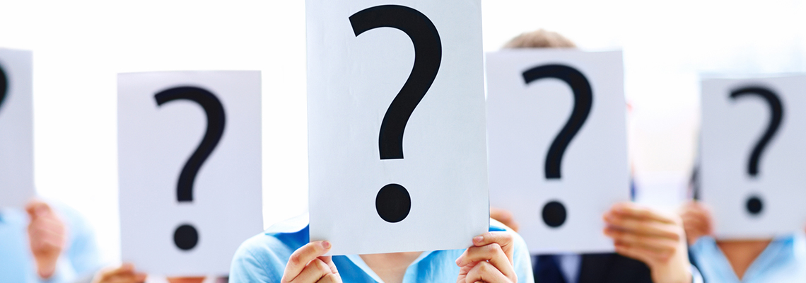 Image of five people holding up question mark signs to obscure their faces