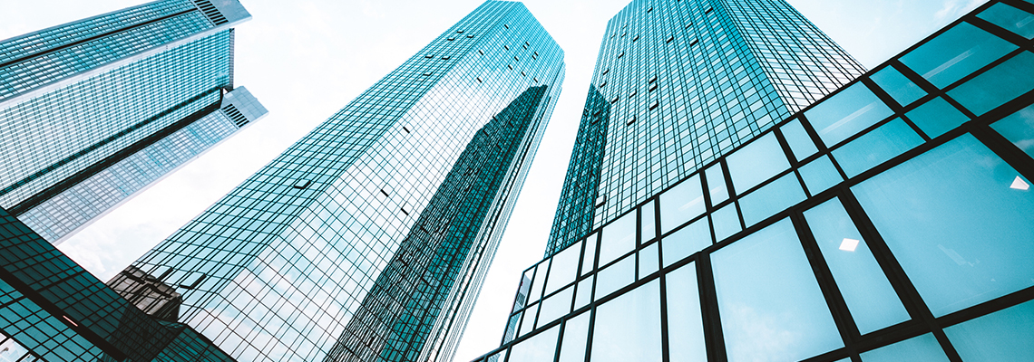 Image of tall glass buildings, view from the ground looking up