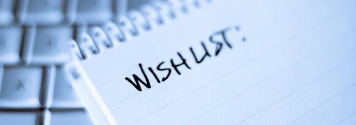 Image of a spiral bound pad of paper with Wishlist written at the top, in front of a computer keyboard