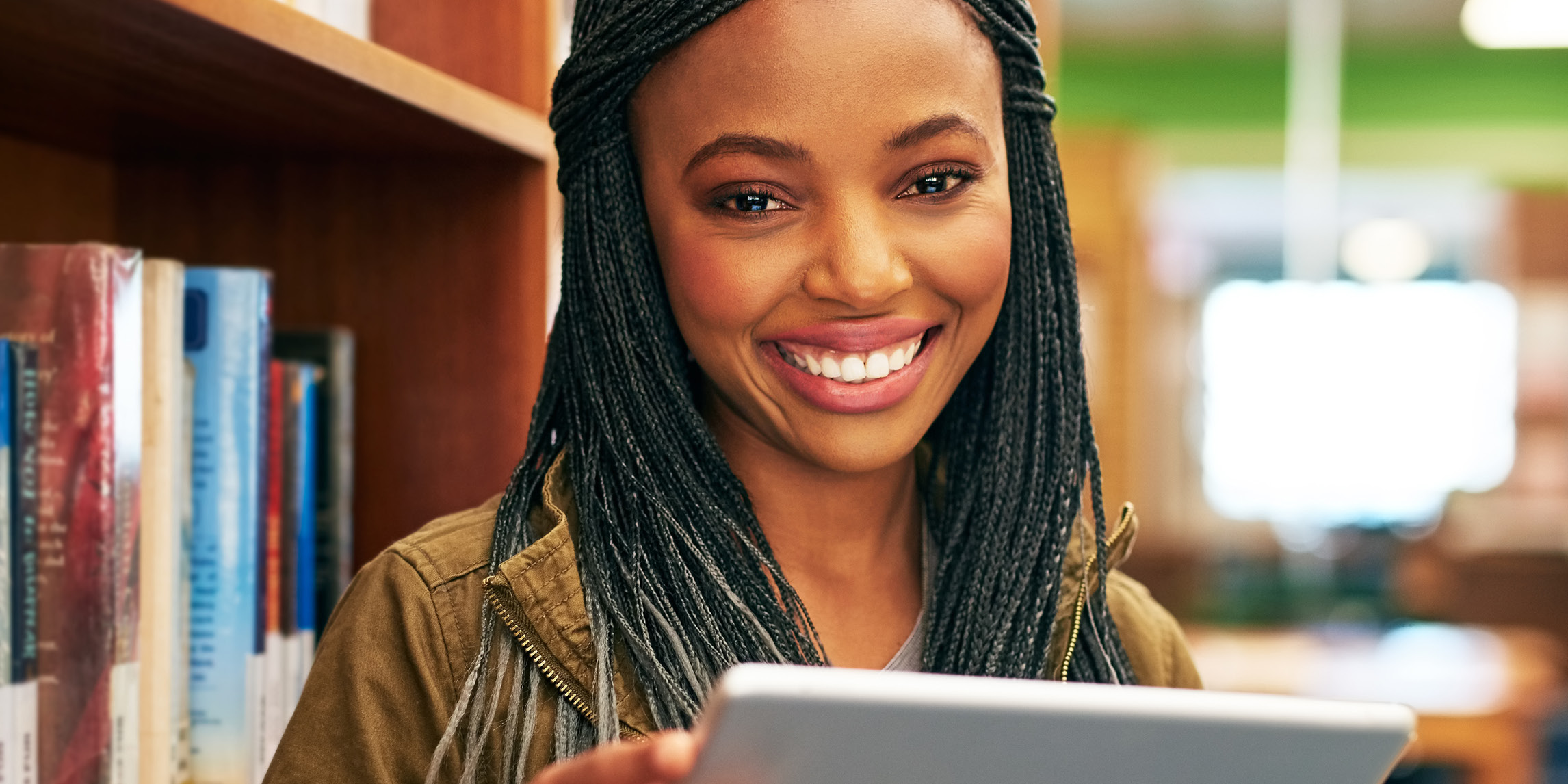 A woman smiling and holding a tablet