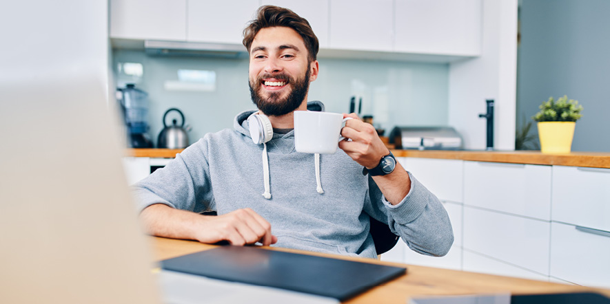 A man smiling and holding a cup in front of a computer